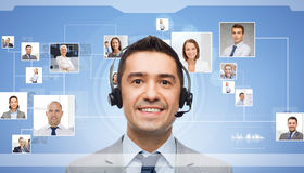 Businessman in headset over contacts icons. Business, people, technology, communication and service concept - smiling businessman in headset and contacts icons Royalty Free Stock Image