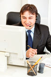 Businessman with headset sitting at office desk Stock Photo