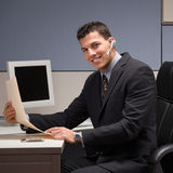 Businessman with headset working at desk. Happy young businessman with headset working at desk in cubicle Stock Photos
