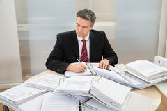 Businessman with heap of folders on desk Stock Photo