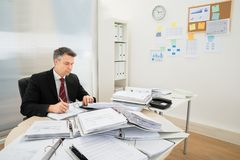 Businessman with heap of folders on desk Royalty Free Stock Photos