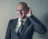 Businessman with hearing problems. A Businessman with hearing problems stock photo