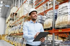 Businessman in helmet with clipboard at warehouse Stock Photography