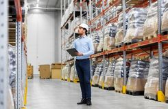 Businessman in helmet with clipboard at warehouse. Logistic business, shipment and people concept - businessman in helmet with clipboard checking goods at Royalty Free Stock Image