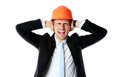 Businessman in helmet covering his ears. Over white background stock photo