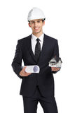 Businessman in helmet hands model house and blueprint. Businessman in white helmet hands model house and blueprint, isolated on white. Concept of real estate and Stock Image