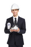 Businessman in helmet hands model house and layout. Businessman in white helmet hands model house and layout, isolated on white. Concept of real estate and Stock Photos