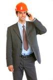 Businessman in helmet on head talking on mobile Royalty Free Stock Photo