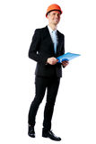 Businessman in helmet holding blue folder Royalty Free Stock Photography