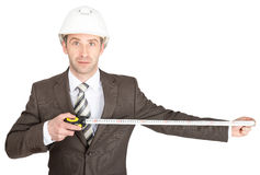 Businessman in helmet holding measuring tape Stock Photos