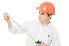 Businessman in a helmet with a meter in his hands. Royalty Free Stock Photos