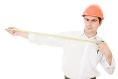 Businessman in a helmet with a meter in his hands. Stock Photography
