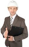 Businessman in helmet offering handshake Stock Images