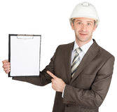 Businessman in helmet pointing on clipboard Royalty Free Stock Photos