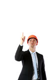 Businessman in helmet pointing up at copyspace Stock Image
