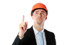 Businessman in helmet pointing up at copyspace Stock Images