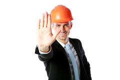 Businessman in helmet showing stop gesture Royalty Free Stock Photo