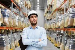 Businessman in helmet at warehouse. Logistic business, shipment and people concept - businessman in helmet at warehouse Stock Photo