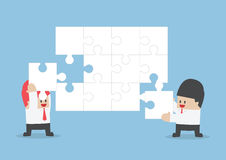 Businessman help each other to assemble blank jigsaw Royalty Free Stock Image