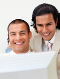 Businessman helping his colleague at a computer Royalty Free Stock Photos