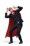 A businessman in a hero red cape and a mask in front view crouching in fear on white background. stock photography