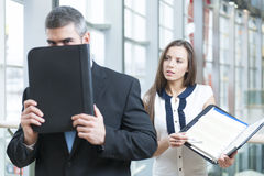 Businessman hides from coworker behind folder Royalty Free Stock Images