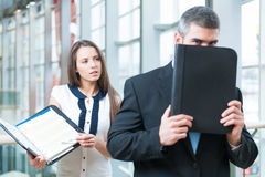 Businessman hides from coworker behind folder Stock Image