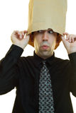 Businessman Hiding. A young businessman hiding his head in a paper bag Stock Photo