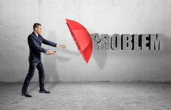 A businessman hiding behind a red open umbrella from a word `Problem` on the wall. Royalty Free Stock Photo