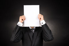 Businessman is Hiding Behind a White Blank Paper Stock Images