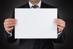 Businessman is Hiding Behind a White Blank Paper Royalty Free Stock Image