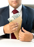 Businessman hiding envelope with money in pocket at jacket Stock Image