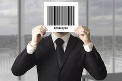 Businessman hiding face behind sign barcode employee. Businessman in black suit hiding face behind sign barcode employee Stock Photo