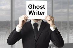 Businessman hiding face behind sign ghost writer Stock Images
