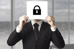 Businessman hiding face behind sign lock symbol Royalty Free Stock Image