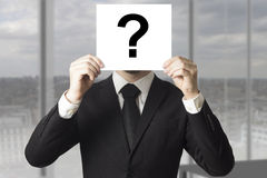 Businessman hiding face behind sign question mark Stock Images