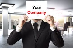 Businessman hiding face behind sign your company Stock Photo