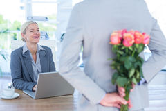 Businessman hiding flowers behind back for colleague Royalty Free Stock Photography