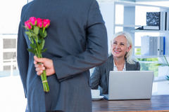 Businessman hiding flowers behind back for colleague Royalty Free Stock Photos