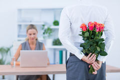 Businessman hiding flowers behind back for colleague Stock Photography
