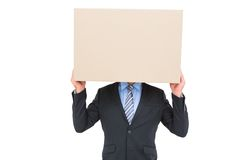 Businessman hiding head with a box Stock Images