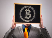 Businessman hiding his face behind bitcoin symbol Royalty Free Stock Photography