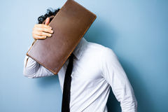 Businessman hiding his face behind an old briefcase Stock Photos
