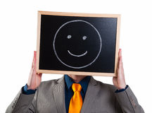 Businessman hiding his face with a white billboard with a smiley Royalty Free Stock Photo