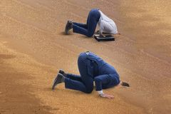 The businessman hiding his head in sand escaping from problems. Businessman hiding his head in sand escaping from problems royalty free stock images