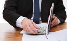 Businessman hiding money in the book Royalty Free Stock Photos