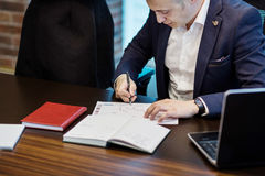 Businessman and his assistant Secretary in his office. The Secretary brought the boss documents to sign,Boss signs the documents royalty free stock images
