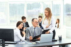 Businessman and his assistants discussed the work plan. Successful businessman and his assistants discussed the work plan stock photography