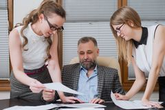 Businessman and his assistants secretaries in his office. Royalty Free Stock Photography