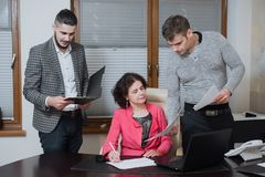 Businesswoman and his assistants secretaries in his office. The secretaries brought the boss documents to sign Stock Photography